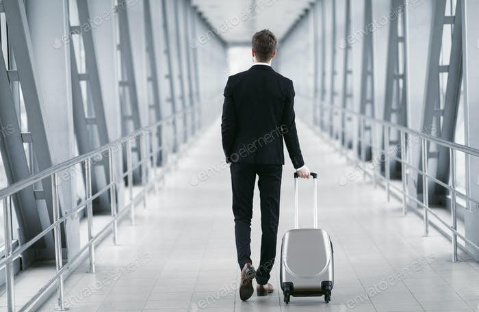 Urban business man walking in airport with suitcase
