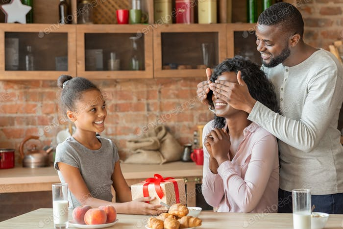 Black father and daughter surprising mother with birthday gift