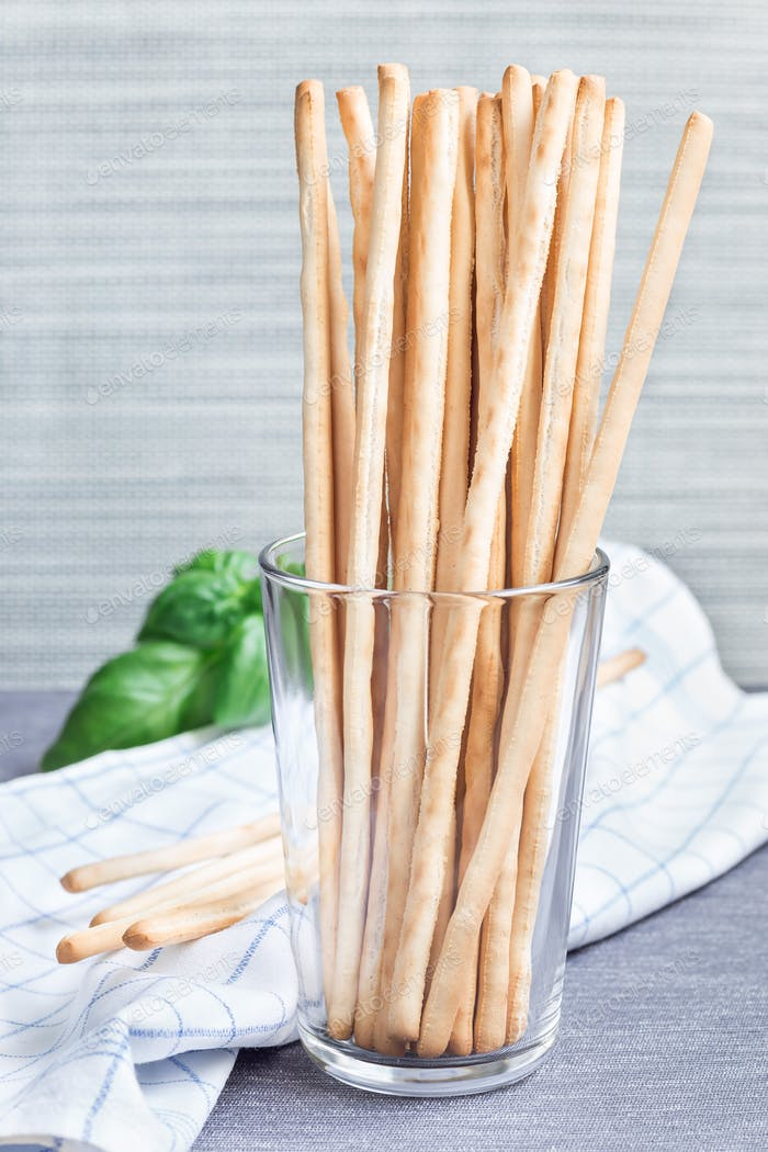 Traditional Italian snack grissini bread sticks in glass with ba