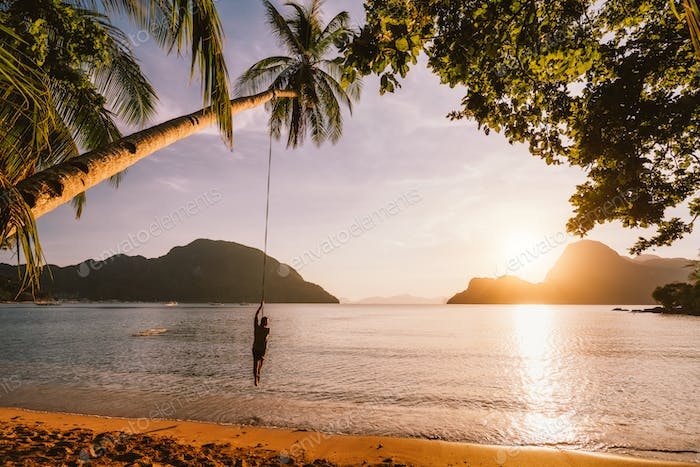 Silhouette of swing men with sunset over tropical island in background. El Nido bay. Philippines