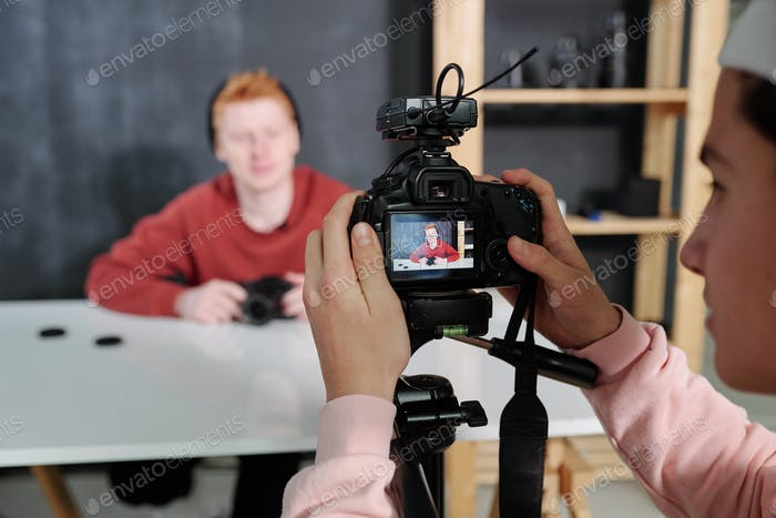 Young video operator holding camera in front of male blogger sitting by desk