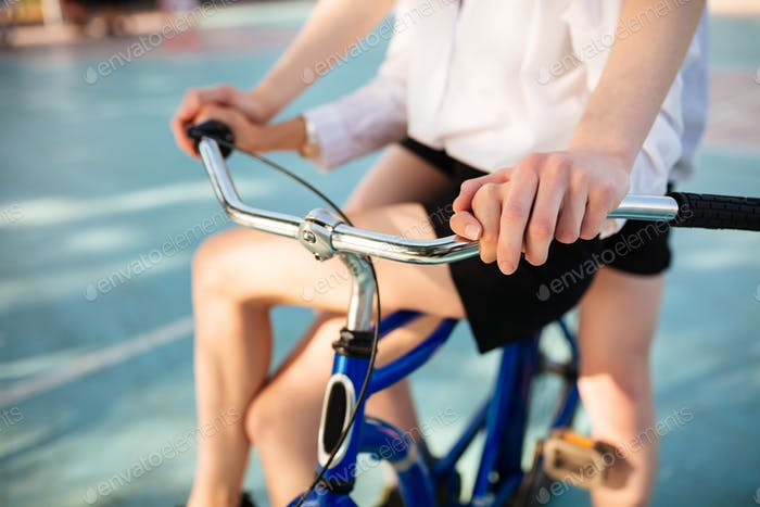 Close up photo of young man and woman bodies riding on blue bicycle together