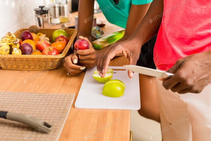 Black African American couple preparing food in the kitchen