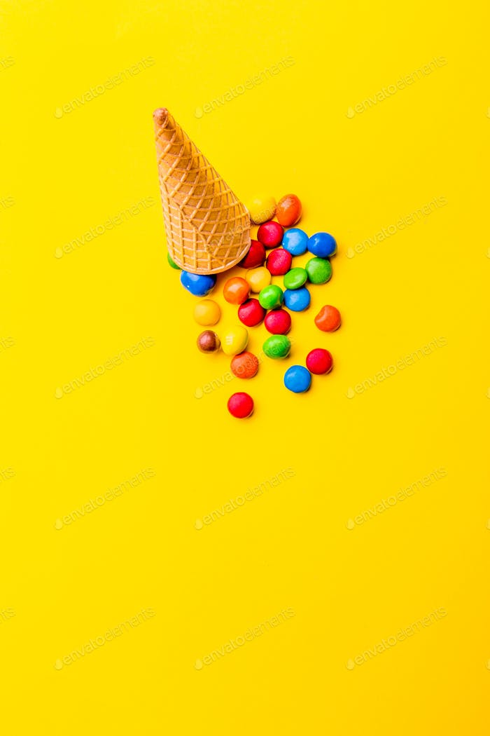 Ice creame cone with candy on yellow background. Minimalistic concept