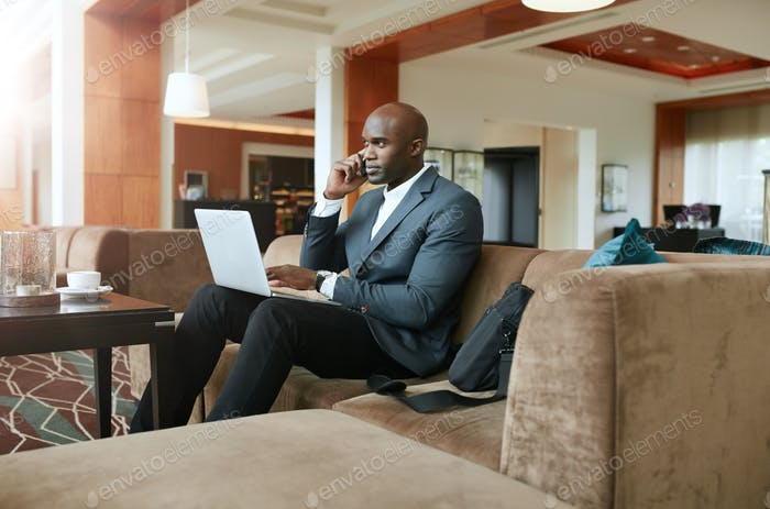 Businessman in hotel lobby using mobile phone