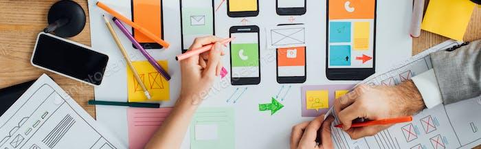 Vista superior de la interfaz de aplicación creativa de los diseñadores para el diseño de la experiencia del usuario cerca de diseños y teléfonos inteligentes
