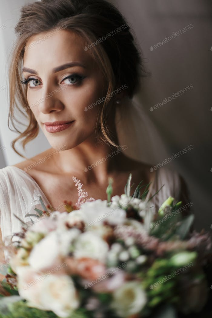 Happy Bride portrait in stylish gown, with perfect makeup, smiling and dreaming
