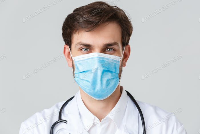 Hospital, healthcare workers, covid-19 treatment concept. Headshot of handsome determined doctor in