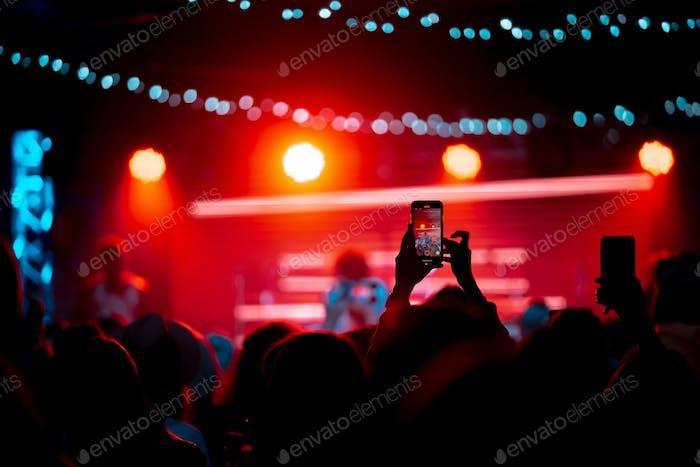 Person hautnah beim Aufnehmen von Video mit Smartphone während eines Konzerts