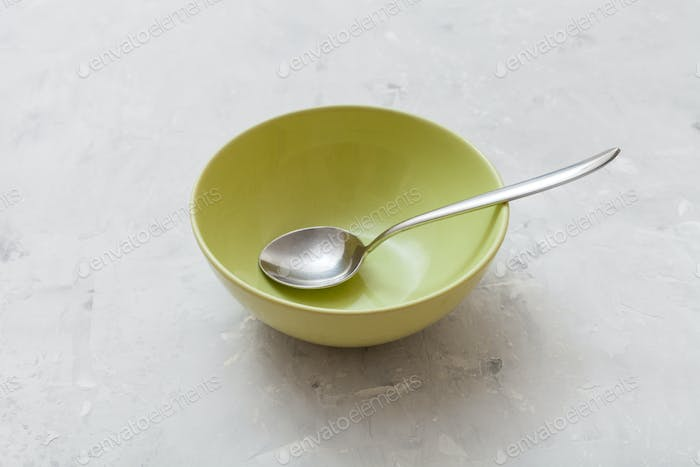 green bowl with metal spoon on gray concrete