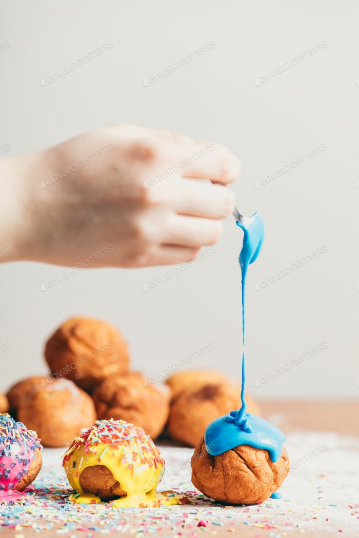 Woman's hand coating a doughnut with blue frosting.