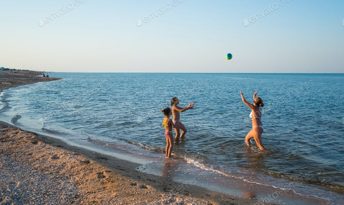 Pretty young woman plays ball with her daughters