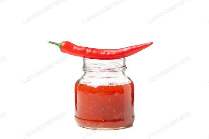 Chili-Pfeffer und ein Glas Sauce einzeln auf weißem Hintergrund