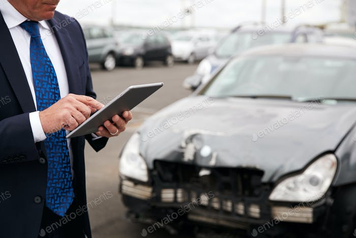 Thumbnail for Male Insurance Loss Adjuster With Digital Tablet Inspecting Damage To Car From Motor Accident