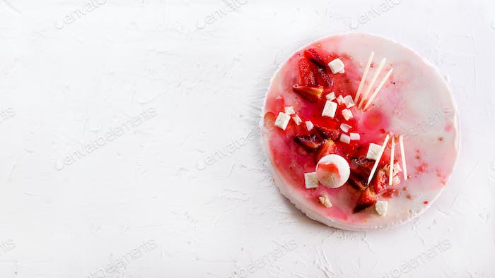 Summer strawberry mousse cake, fresh berries, coconut, and sweet decor element on top, white