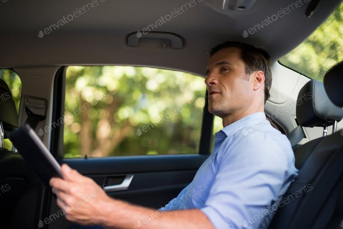 Man holding digital tablet in car