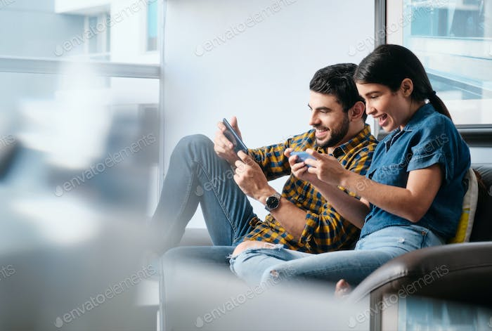 Young Couple Playing Video Game on Phone at Home