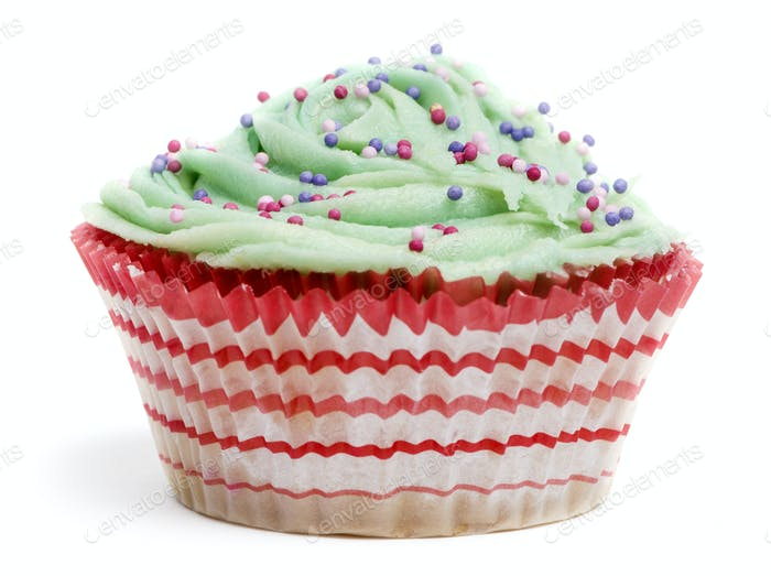 Cupcake with green icing and hundreds and thousands against white background