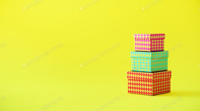 Collection of colorful gift boxes on yellow background. Banner. Presents for birthday party