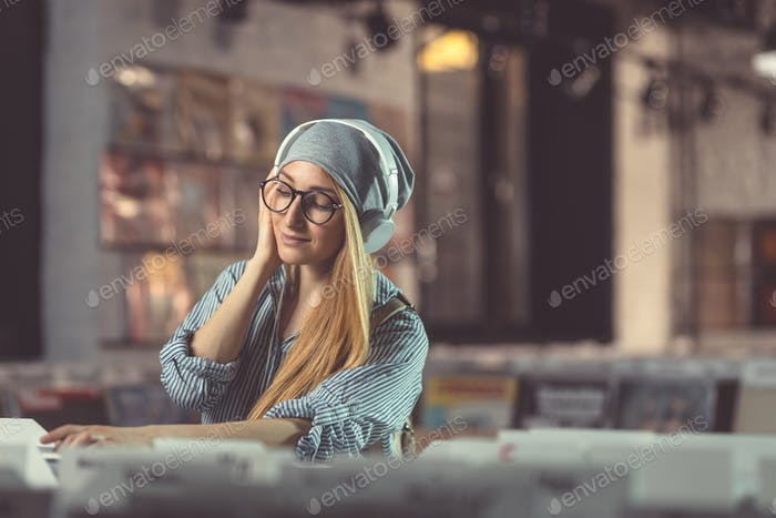 Young girl listening to music with headphones indoors