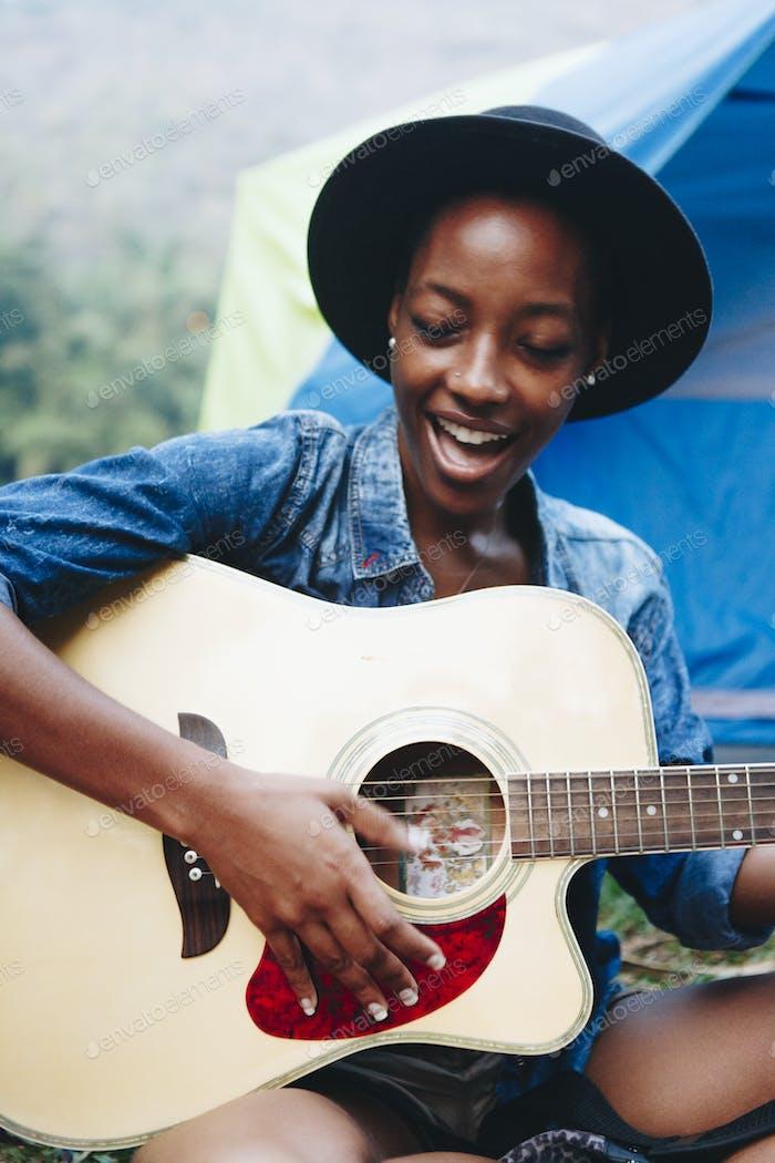 Gruppe junger erwachsener Freunde auf dem Campingplatz Gitarre spielen