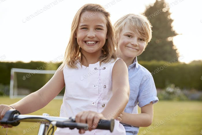 Two children riding a bicycle in the garden
