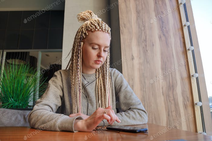 Worried young hipster woman in cafe. Lateness or punctuality concept.