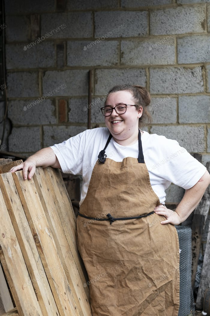 Portrait of female baker outdoors, hand on hip, smiling at camera.