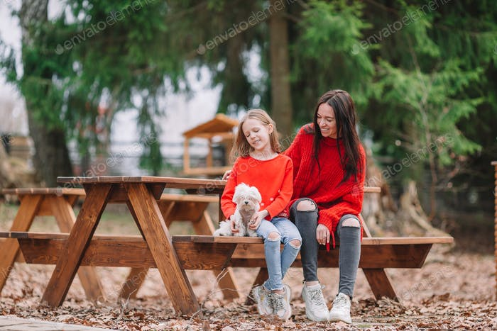 Adorable little girl and young mother with puppy outdoor