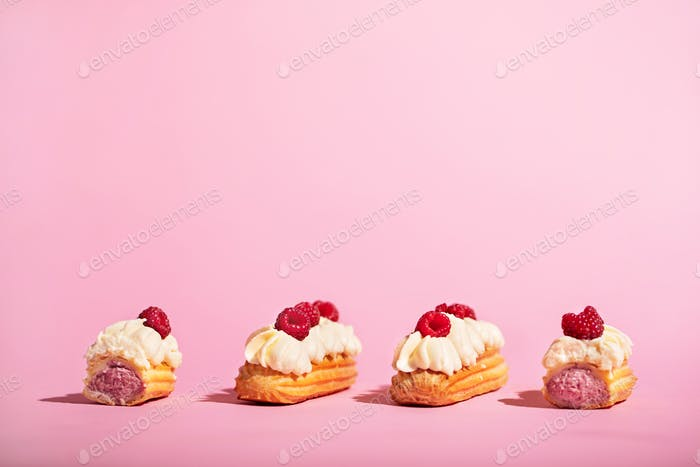 Four colorful eclairs with raspberries on pink background.