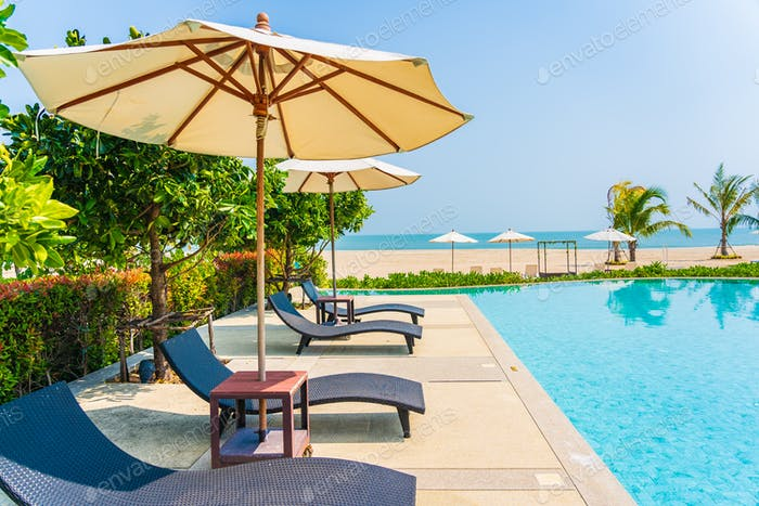 Umbrella and chair around outdoor swimming pool in hotel resort