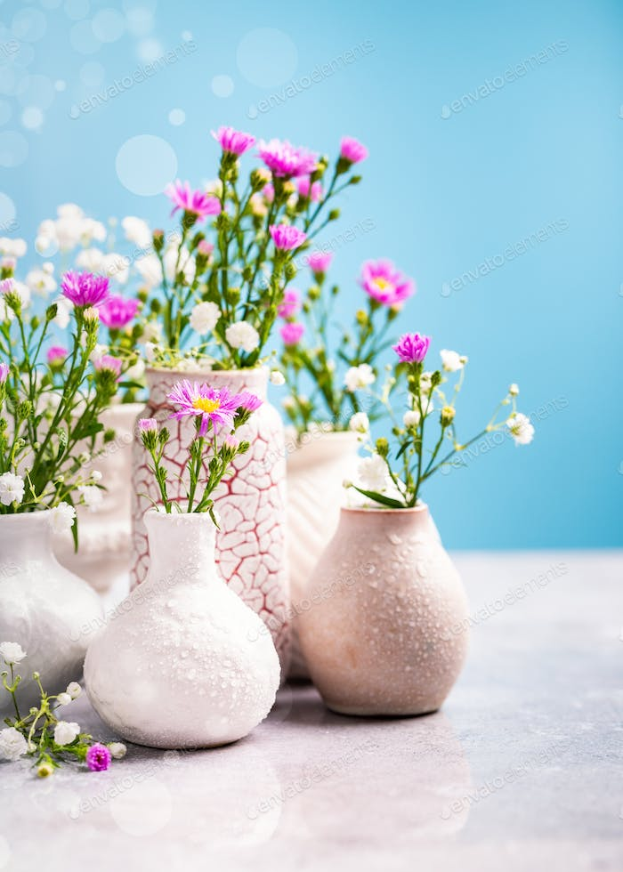 Vase with beautiful flowers on light table