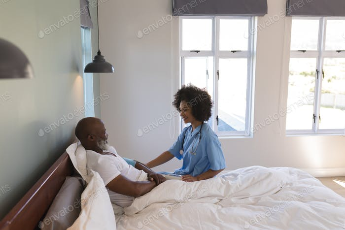 Female doctor consoling senior man in bedroom at home