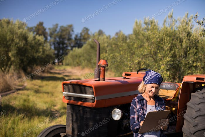 Woman leaning on tractor while writing on clipboard