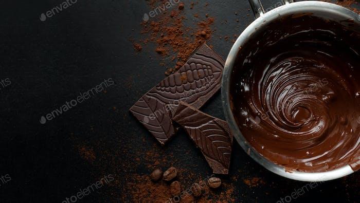 Melting chocolate in pot on dark