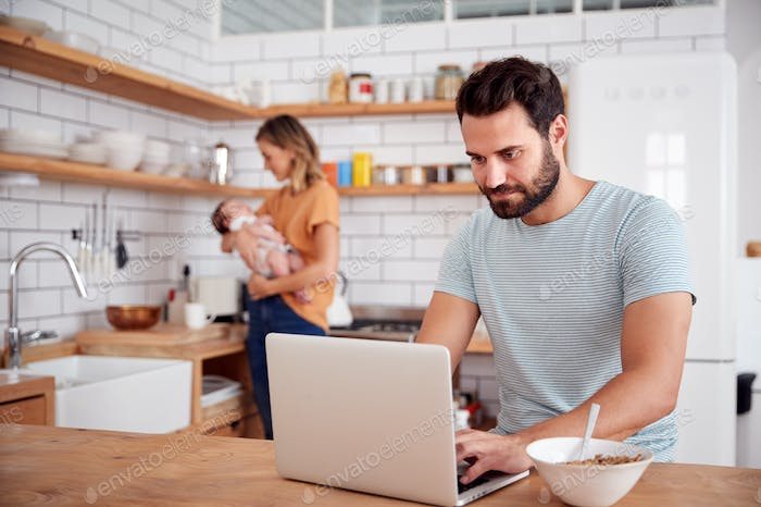 Multi-Tasking Mother Holds Baby Son And Makes Hot Drink As Father Uses Laptop And Eats Breakfast