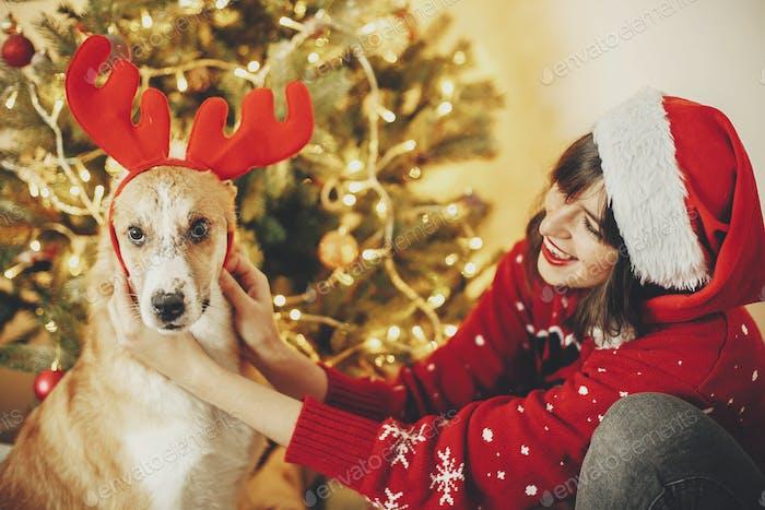 Girl putting on cute dog reindeer antlers