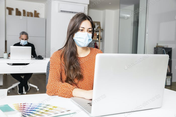 Business woman wearing a mask sitting in office.