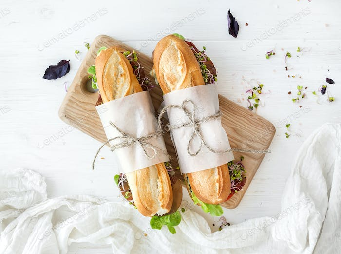 Sandwiches with beef, fresh vegetables and herbs on rustic wooden chopping board