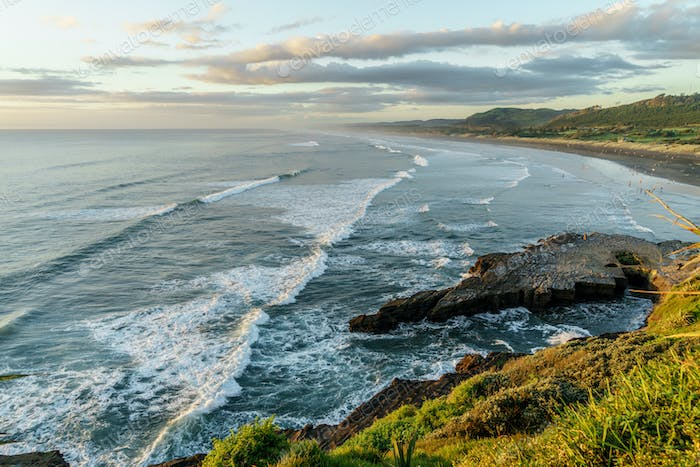 aerial view of wavy ocean and rocky coast on sunset, New Zealand