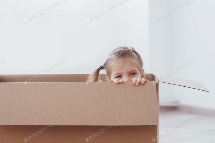 Child preschooler boy playing inside paper box. Childhood, repairs and new house concept