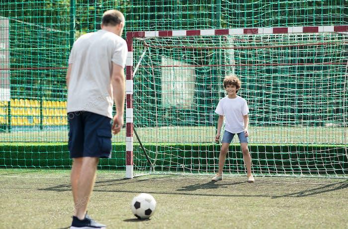 Kleiner Junge spielt Fußball mit seinem Vater