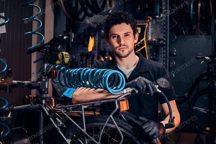 Handsome talented master is fixing bicycle at his own workshop using pneumatic tool