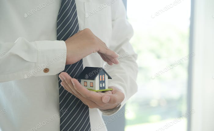 Insurance agent hold a house model in hand showing the symbol of home insurance.
