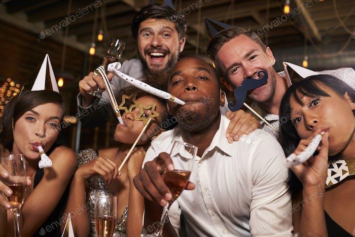 Friends having fun celebrating New Year at a bar, close up