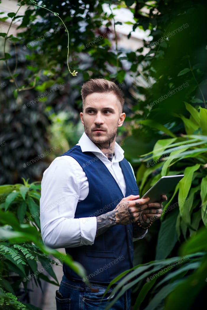 Young man with tablet standing in botanical garden
