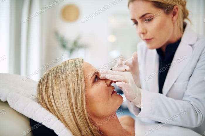 Female doctor injecting botox into a mature woman's forehead