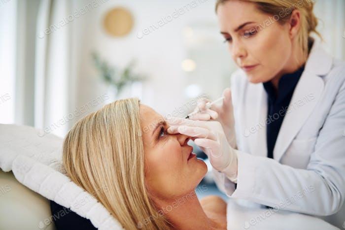 Médico Mujer inyectando botox en la frente de una Mujer madura
