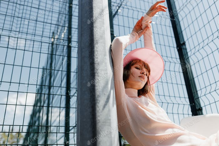 Stylish girl in a gently pink dress and pink visor sitting on a chair behind fence of the lattice at