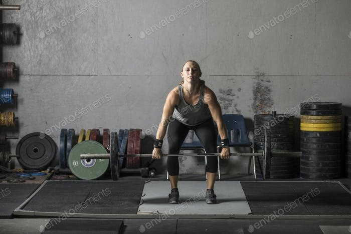 Young athletic woman training with heavy weights.